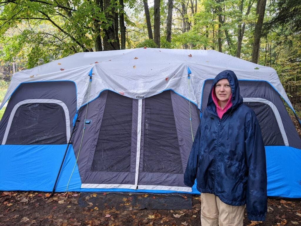 FIRE Travel Family - New York - Becky Taking Tent Down in the Rain - Financial Independence - Retire Early